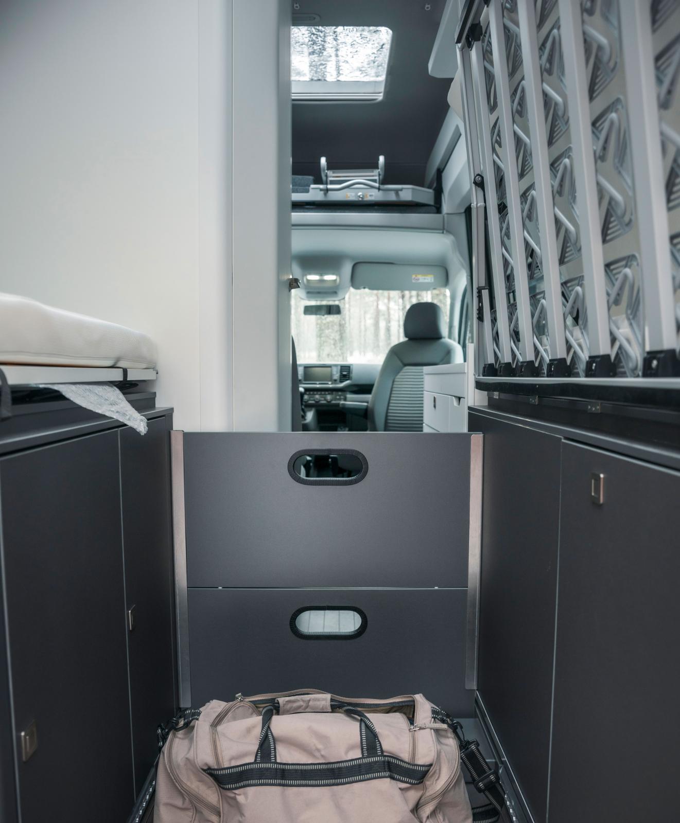 Lastförskjutningsskydd av stabilt skivmaterial. Ett lastnät vore bättre då skivorna tar stor plats när de inte används.
