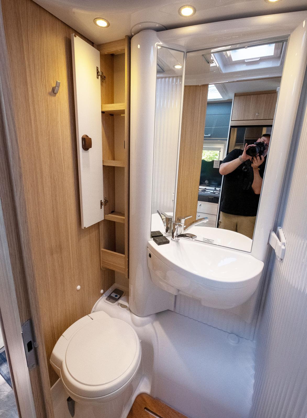 """Klassiskt badrum med """"svängvägg"""" i normalläge. Bra med hyllförvaring och krok för handduk."""