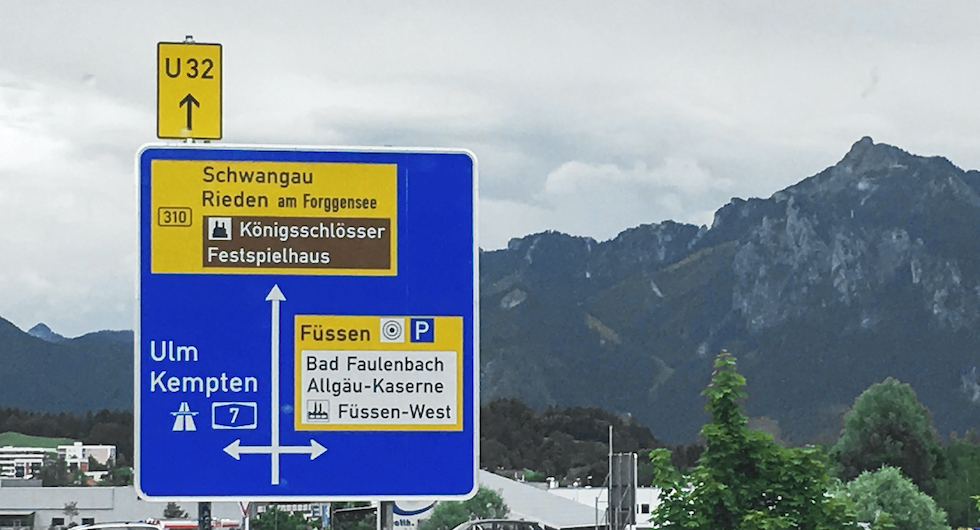 """SÅ LÄSES SKYLTEN. Rakt fram """"Umleitung"""", tillfällig omdragning av väg. Även Bundesstrasse (gul skyltning) mot ett slott och längre bort Rieden och längst bort ligger Schwangau. (Ju högre upp på skylten betyder desto längre avstånd dit).  Till höger ligger Füssen där det finns en p-plats med vacker utsikt. Sväng vänster för att komma till Autobahn A7 mot Kempten och Ulm (blå)."""