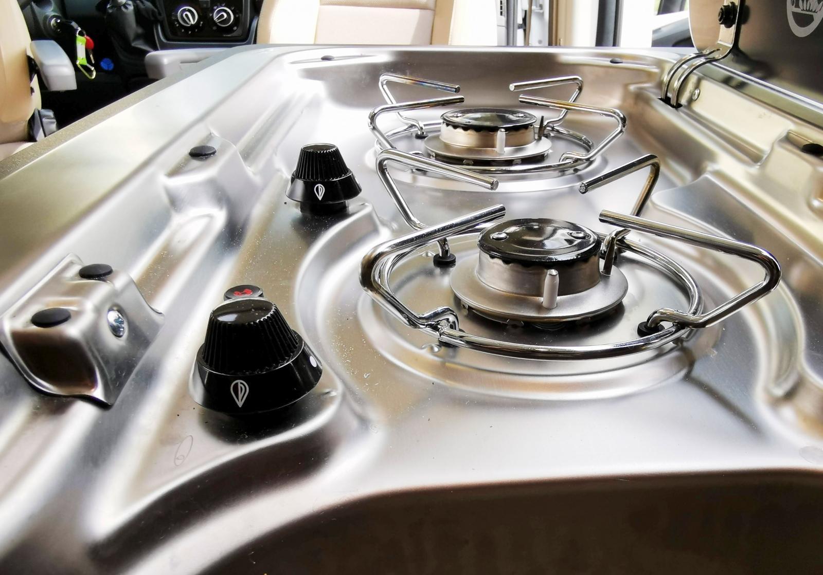Köket med tvålågig spis i samma enhet som diskhon.