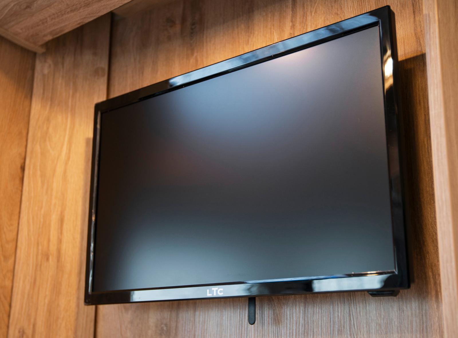 En tv-skärm är fast monterad på väggen vid entrén.