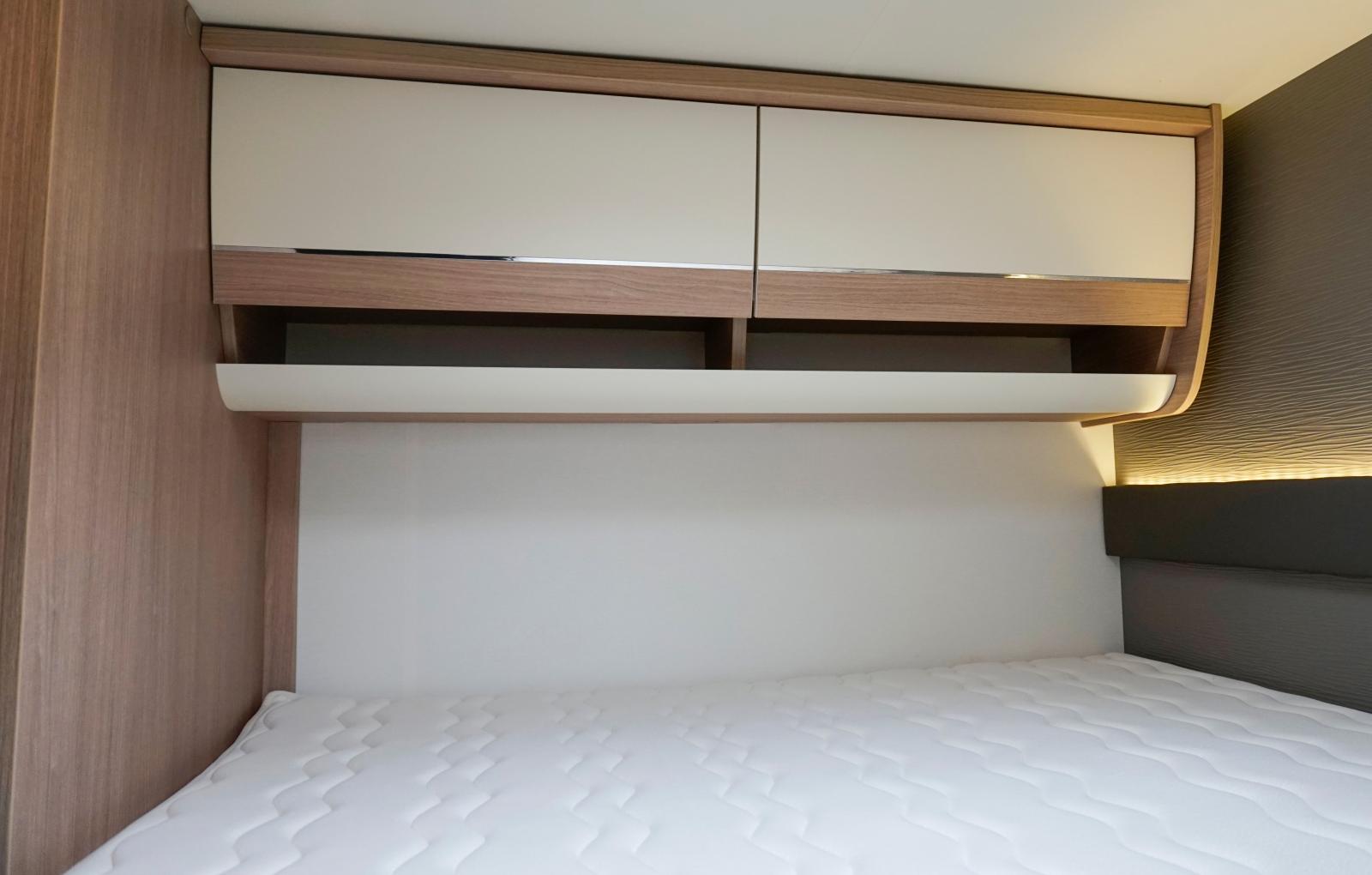 Överskåp på ena sidan, läslampor och fönster på andra sidan. Snygg väggpanel kallad TEP.