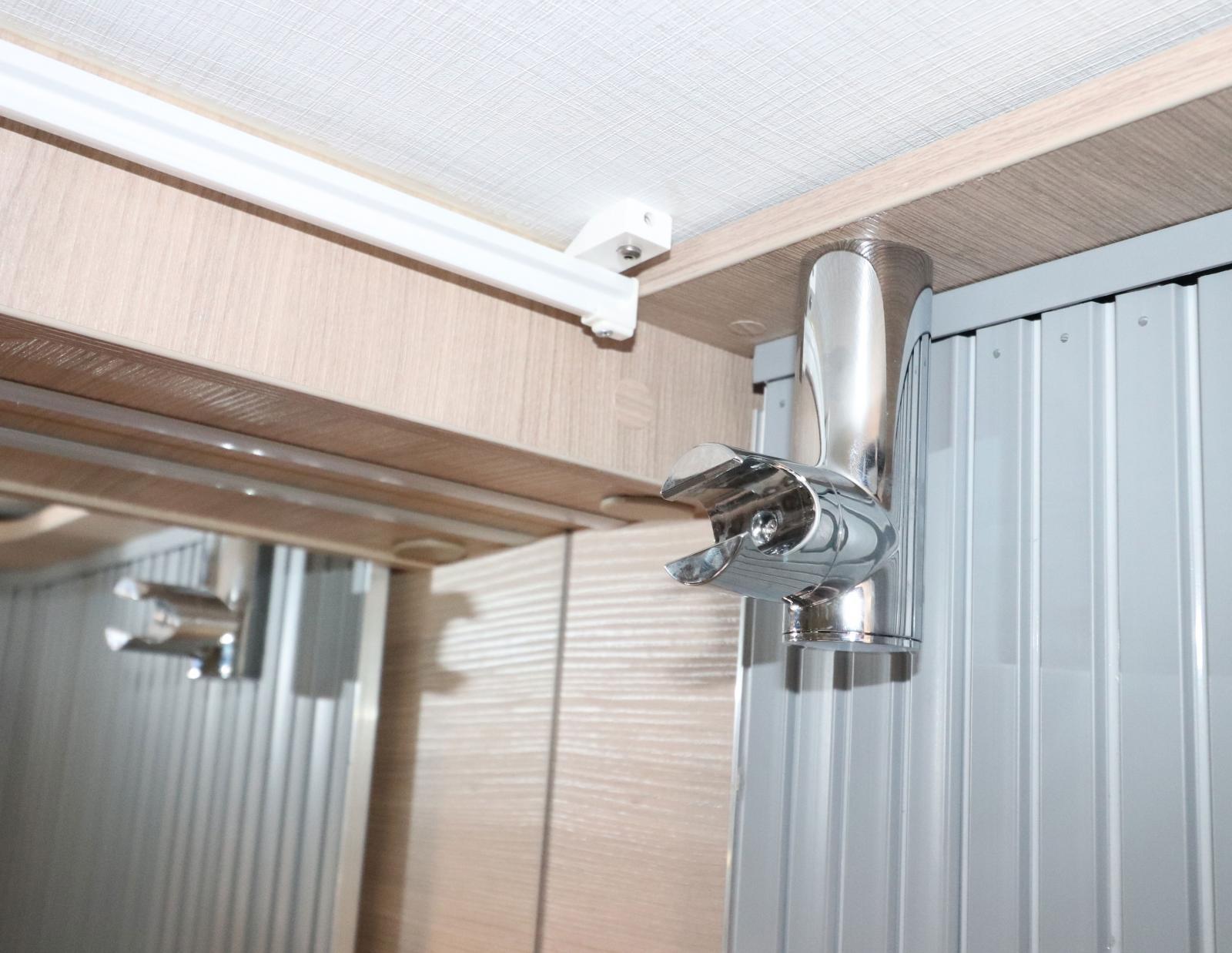 Kranen till handfatet kan dras ut och fästas i taket.