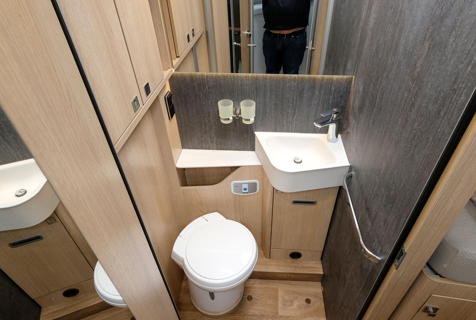 Toalett och handfat i ett utrymme där trivseln är hög tack vare bra förvaring, snygga väggar, kontakter och mugghållare.