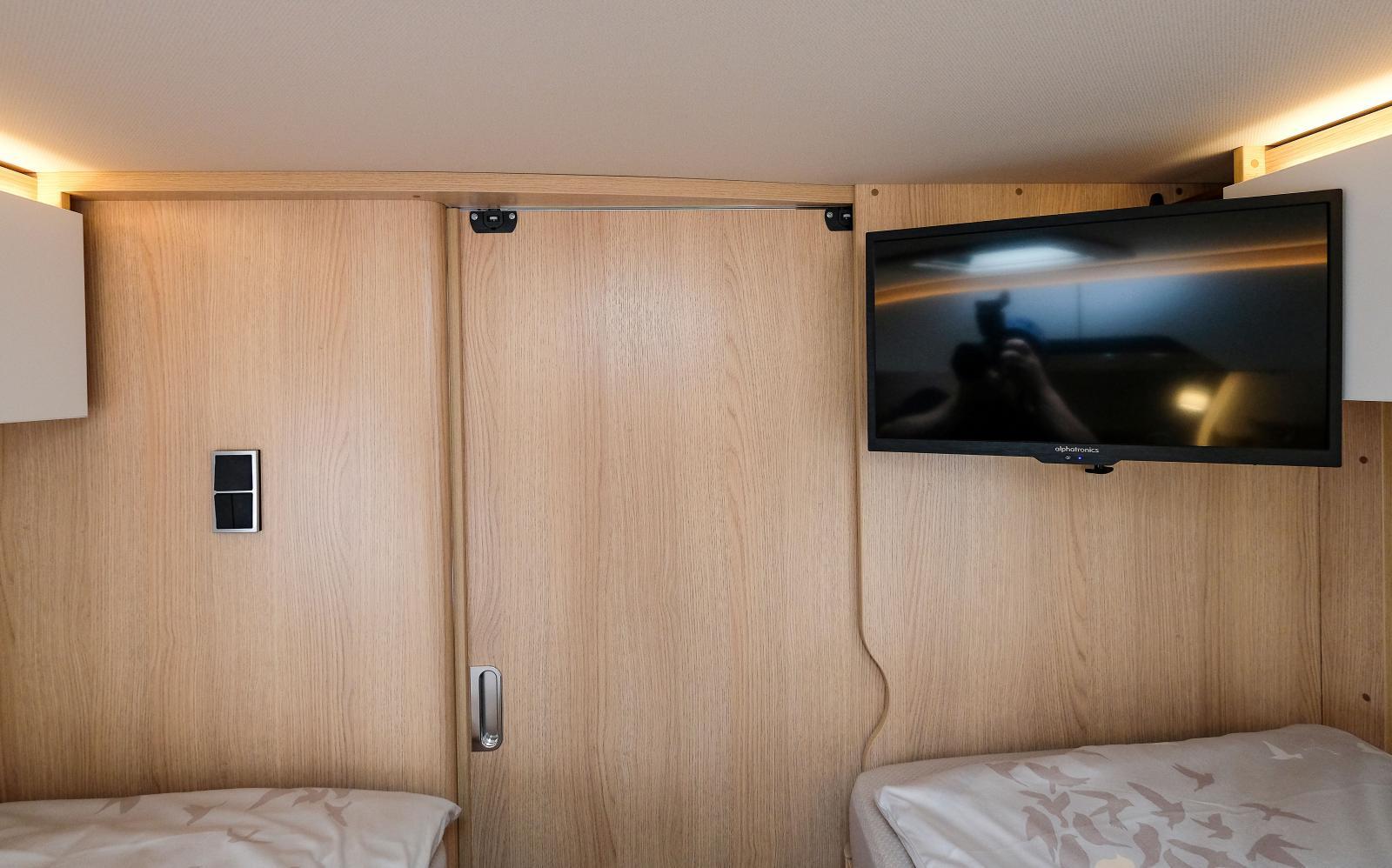 Sovrum med bra placering av tv och skjutdörr mot badrum.