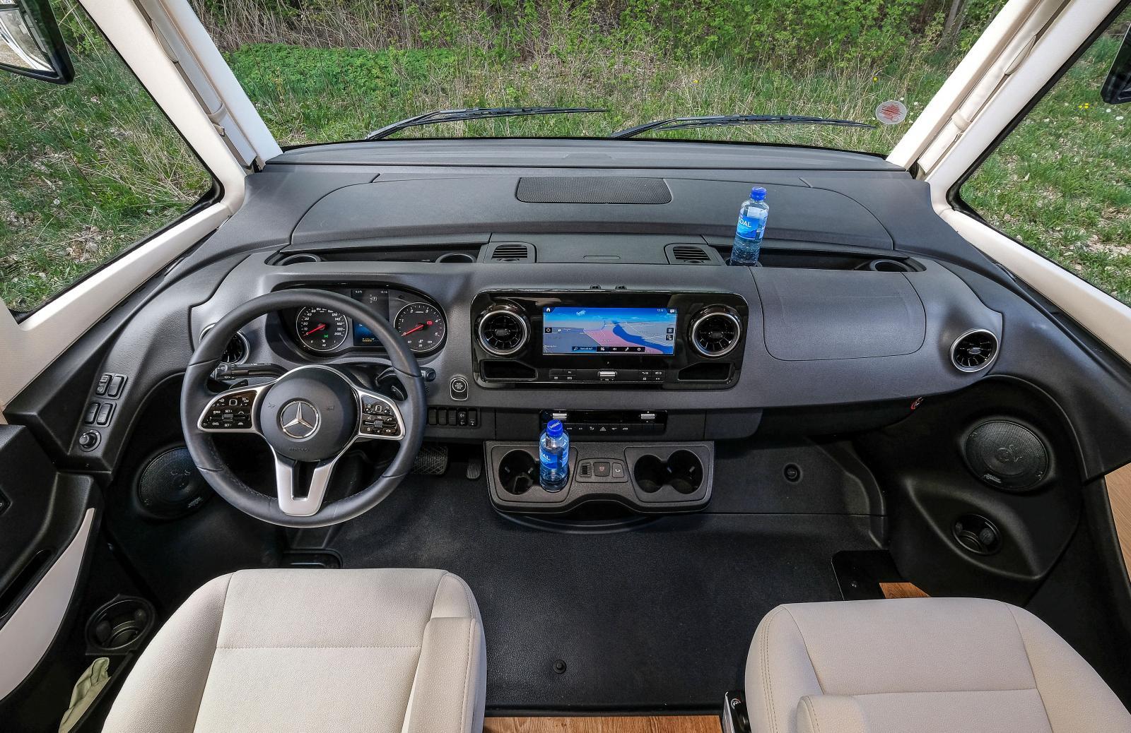 Mängder av förvaringar och drickahållare i nya Mercedes-Benz Sprinter. Treekrad ratt fylld med knappar och bra skärm i mitten