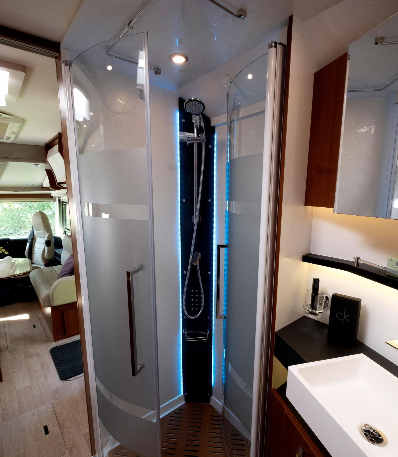 Duschkabinen är placerad jämte handfatet på bilens högra sida. Trätrall på duschgolvet och handduksstång i duschens tak.