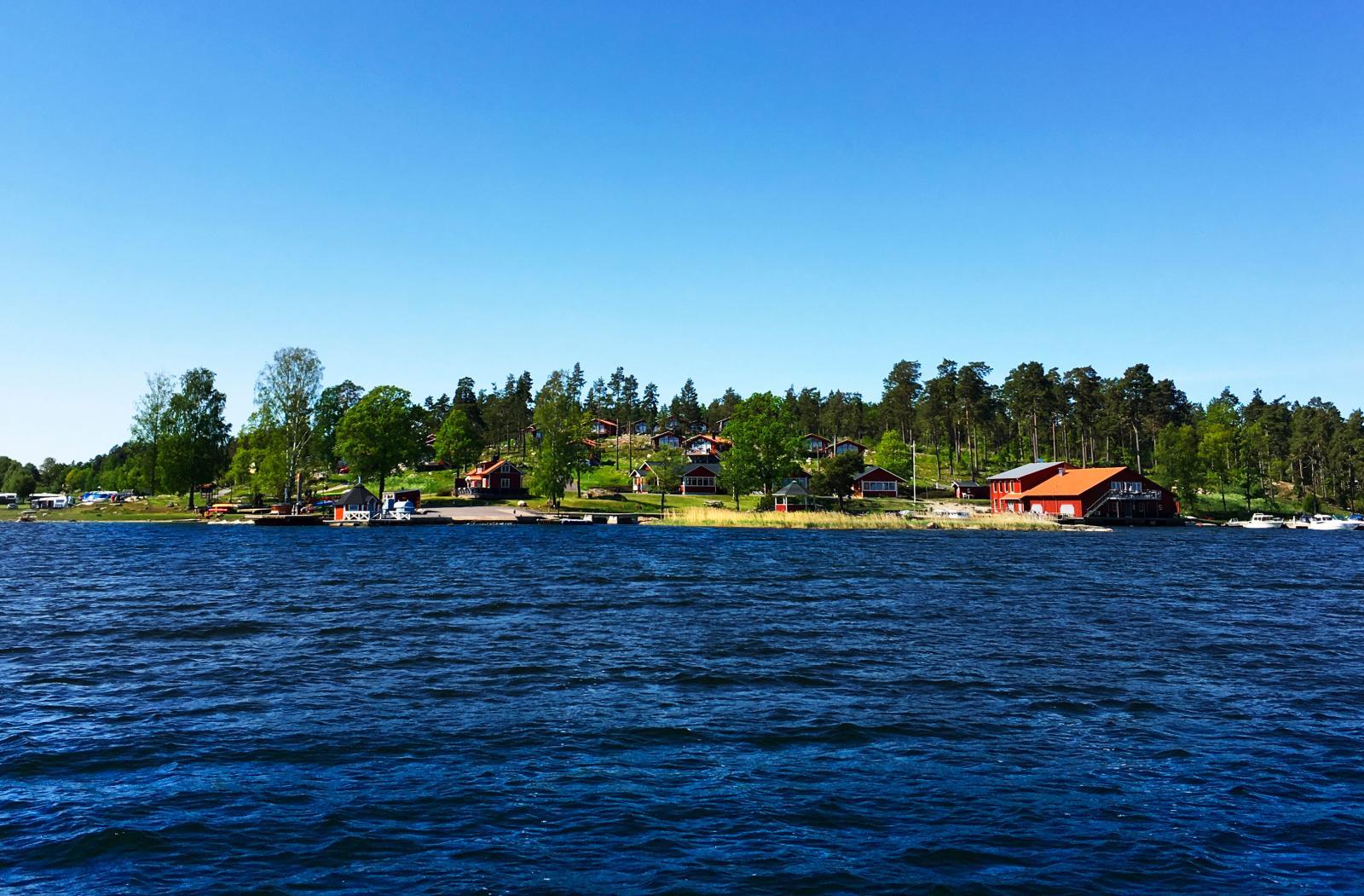 Camping sedd från havet med det faluröda båthuset längst till höger.