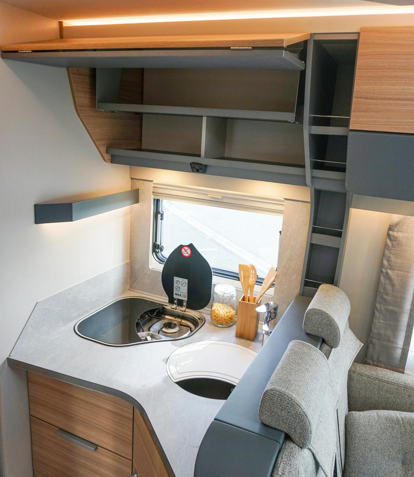Köket är kompakt i vinkel men smart utformad köksbänk och hyllplan ger bra förvaring.