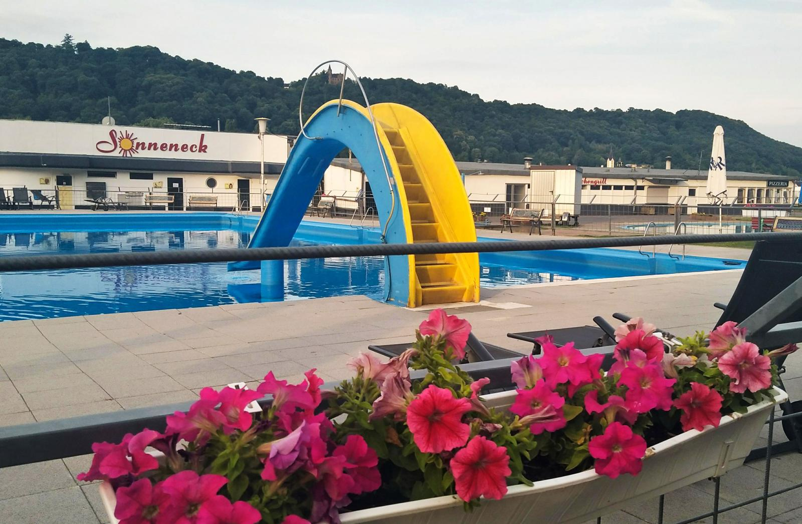 Rejäl swimmingpool med solstolar och rekordkort vattenrutschbana. Plaskdamm för de yngsta till höger.