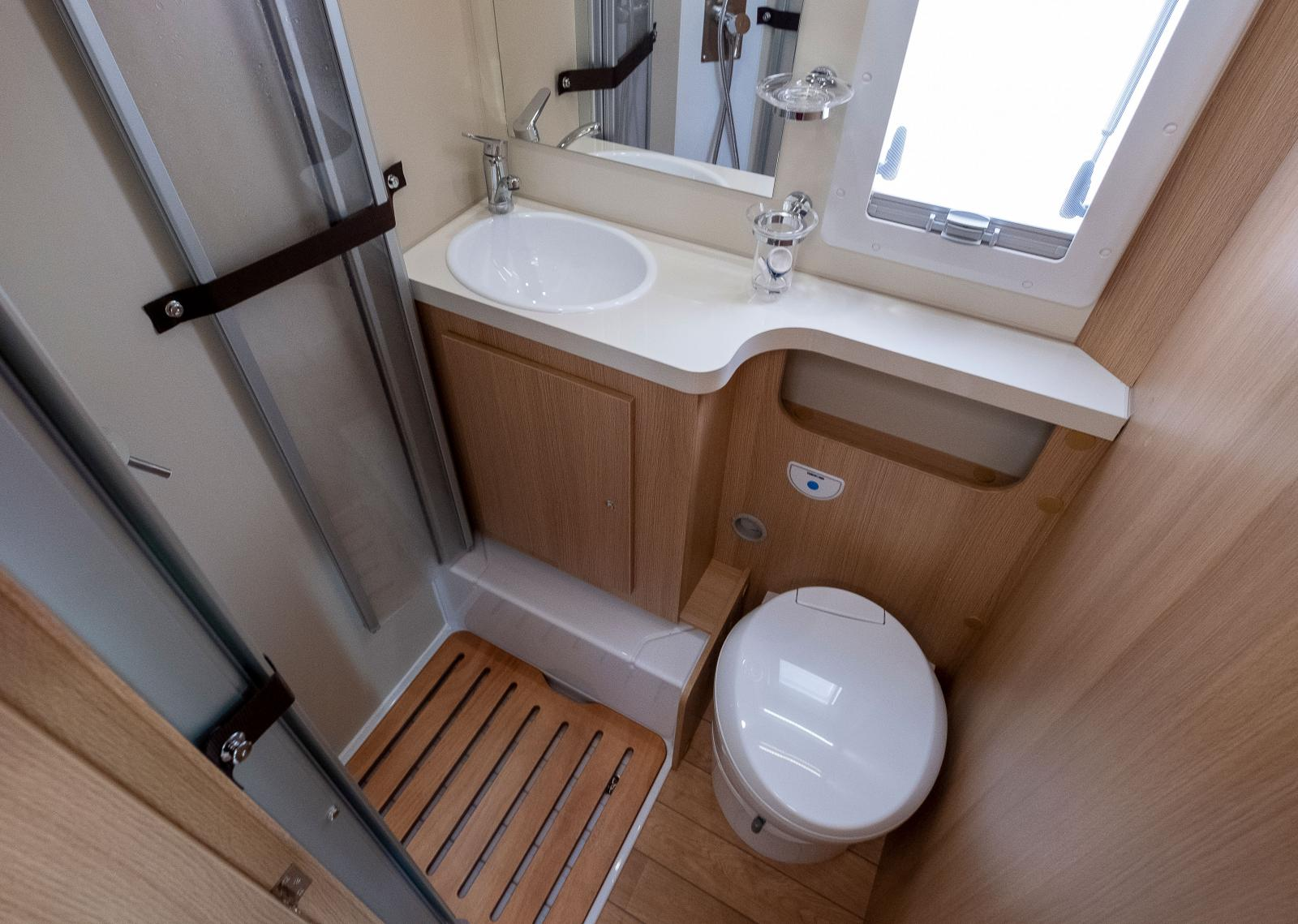 Ljust och fräscht i badrummet. Duschdörrarna kan spännas fast.