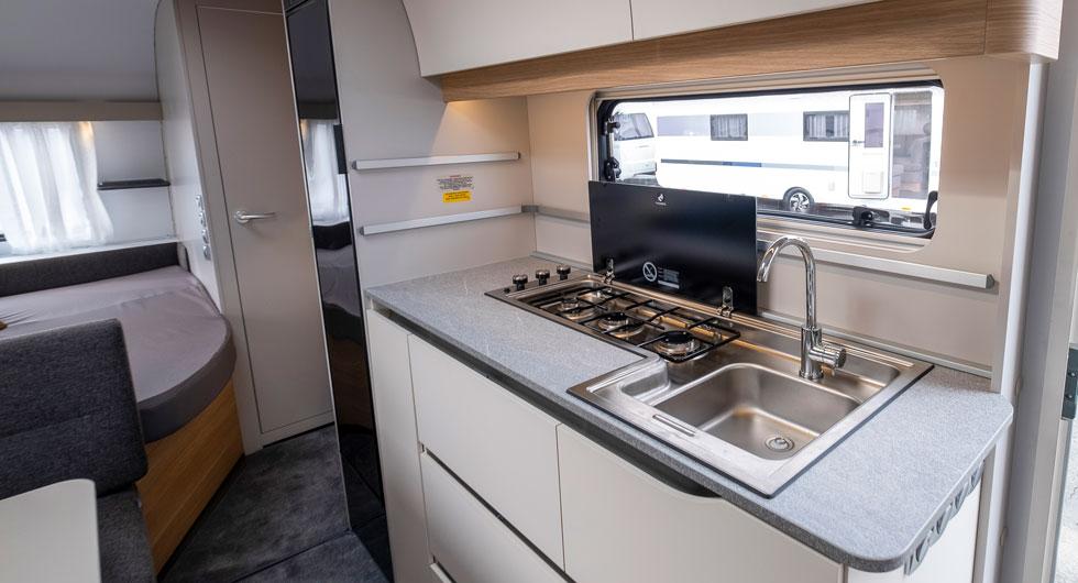 Köksbänken är lång och diskhon och spisen är enkla att hålla rena.