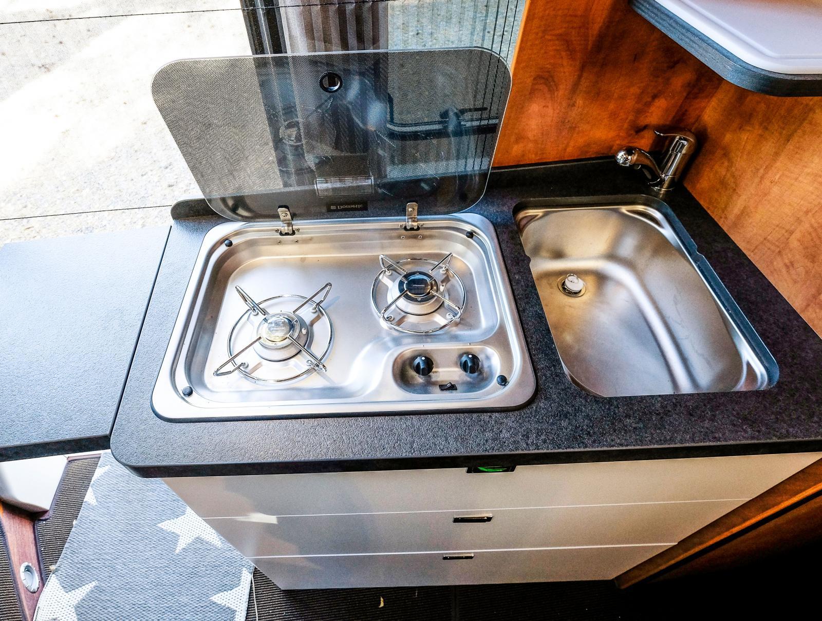 Köksmodul i en Malibu plåtis med uppfällbar avlastningsyta. Med skjutdörren öppen får man god köksventilation.