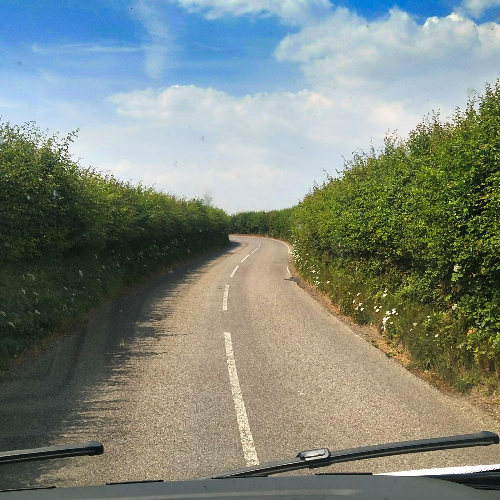Vägen till campingen är kantad av buskage. Är det inte stenmurar så är det träd, staket eller buskar som är närgångna.