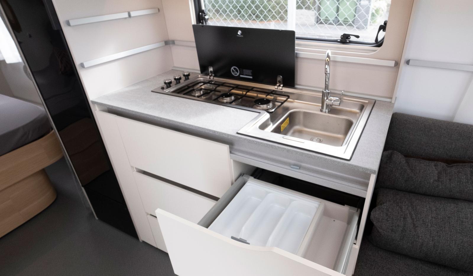 Köket i Adria Adora 613 UT. Färgsättningen är kontrastrik.