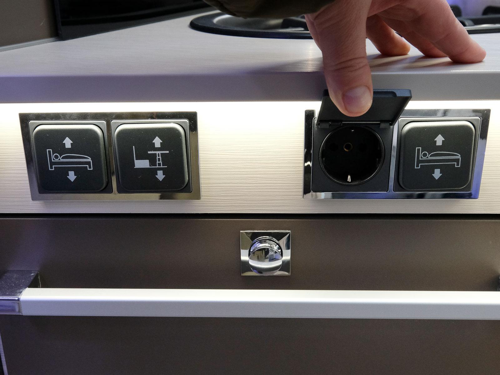 Elreglage för sängar och matbord samt 230V uttag finns under köksbänken.