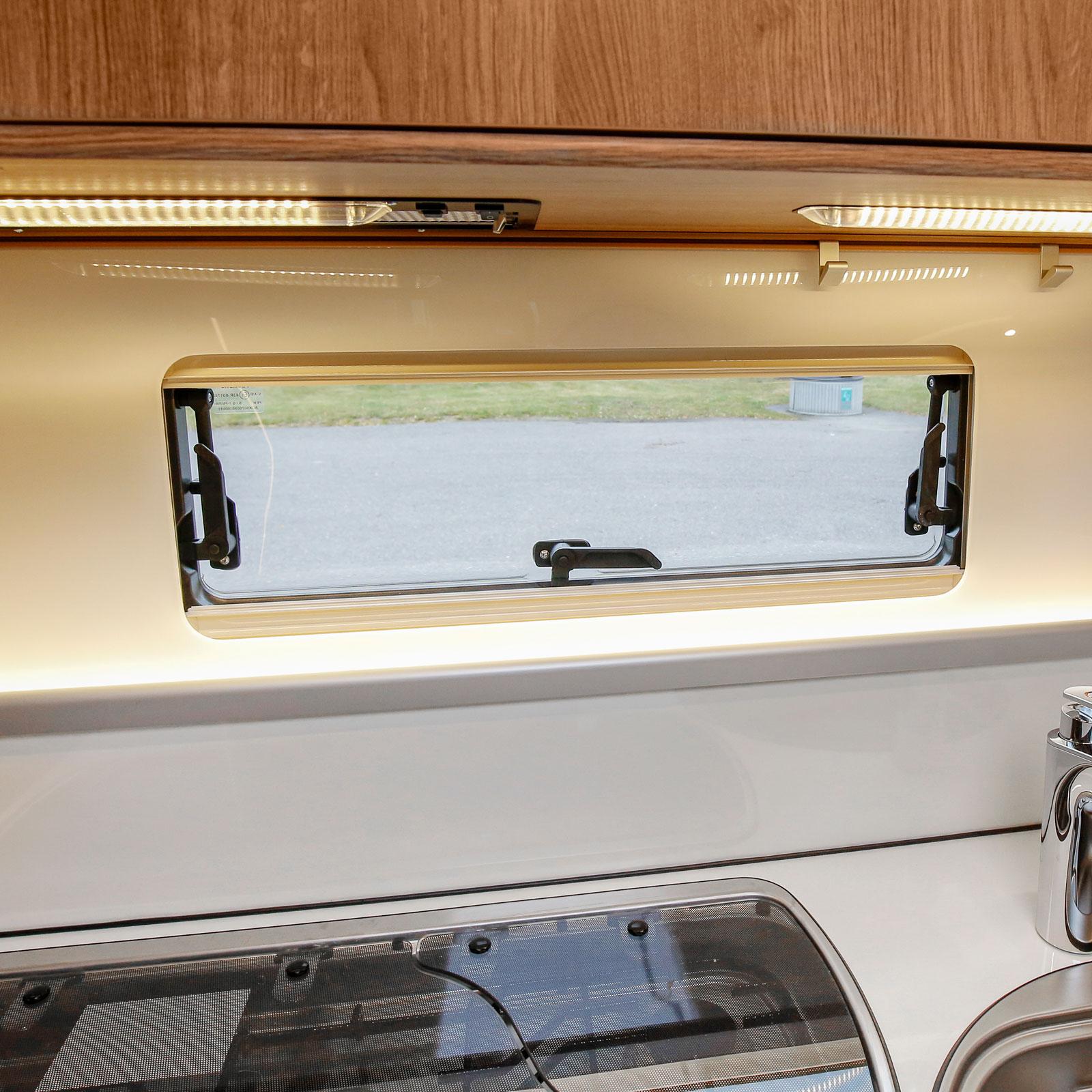 Köksväggen är elegant med ett brett köksfönster.