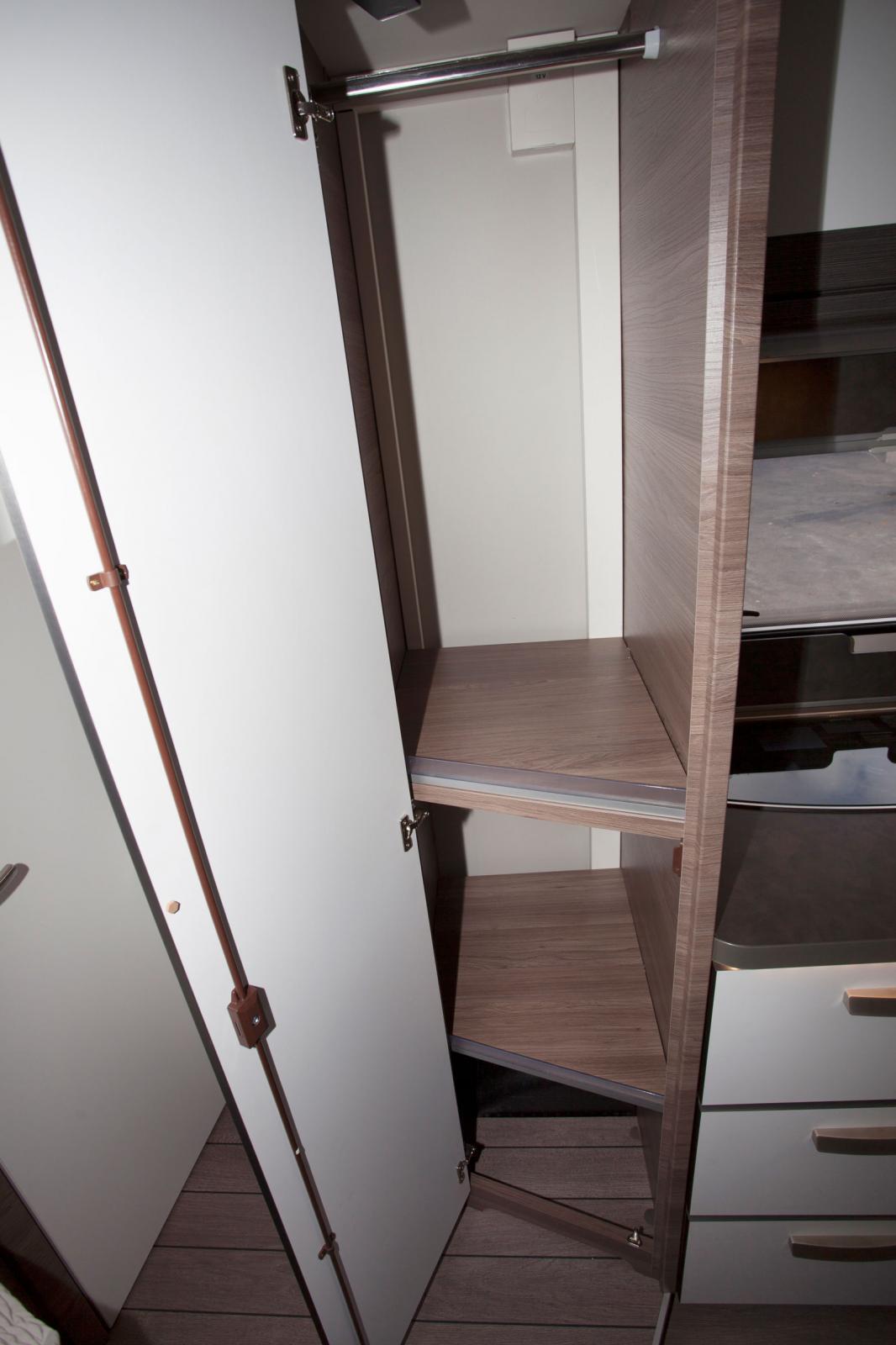 En garderob med klädstång är placerad mellan kök och badrum.