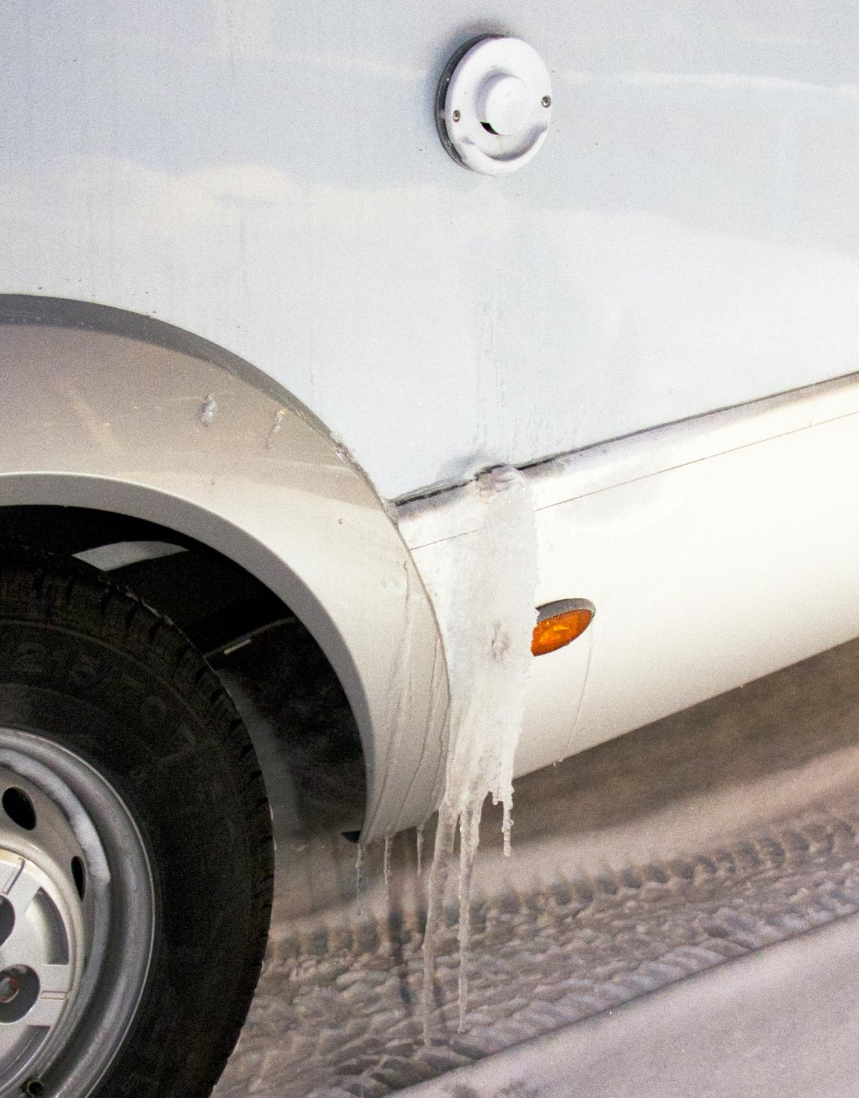 Avgasutblåset värms och kondensvattnet fryser fast i sidan av bilen.