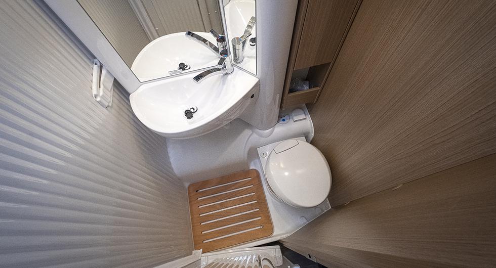 Badrummet har en vikvägg som fäller undan handfatet åt sidan. Ingen kommod under handfatet men väl några hyllplan intill.