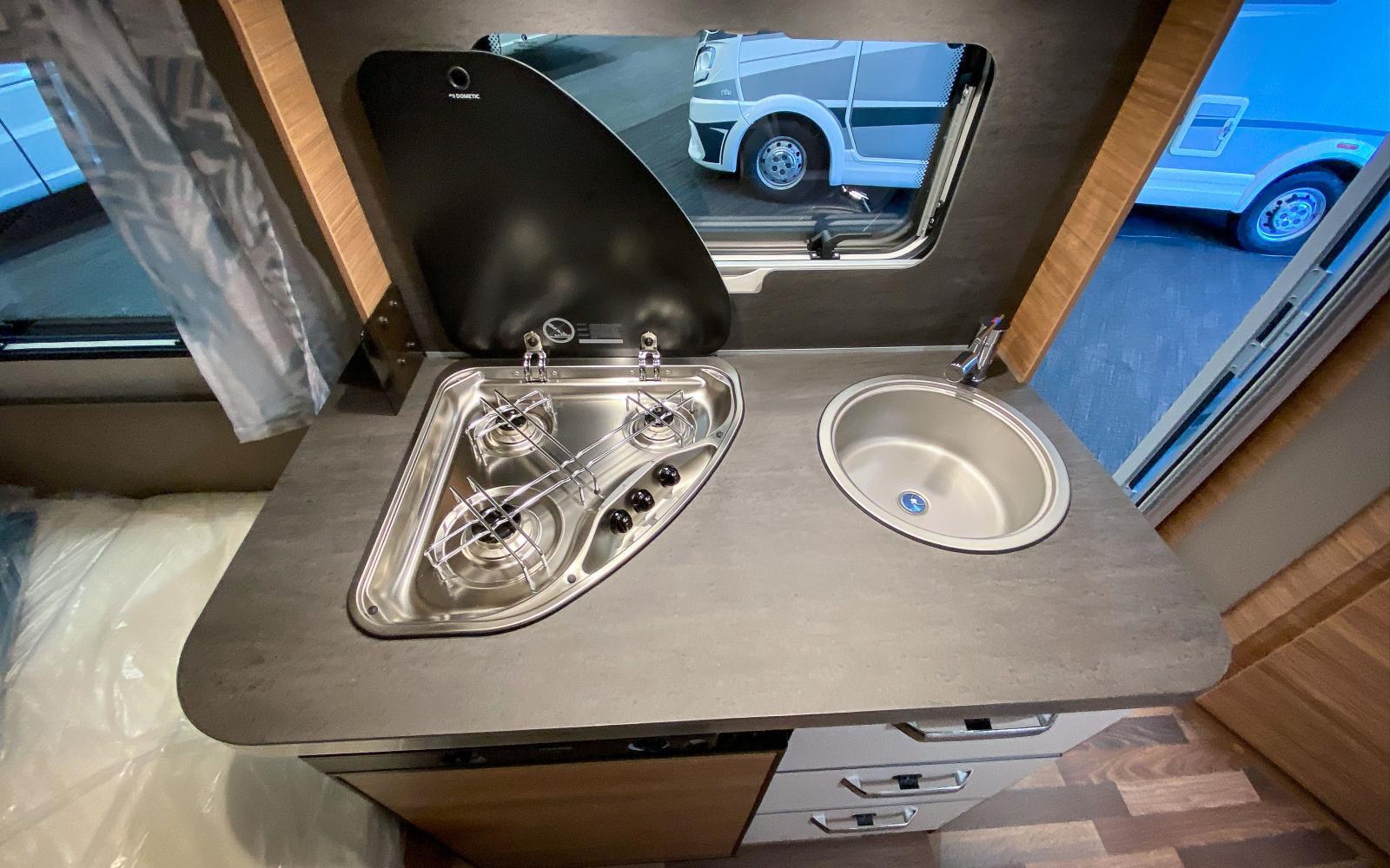Köksbänken består av spis och diskho. Tre spislågor och ett kylskåp på 106 liter och viss arbetsyta runtom.