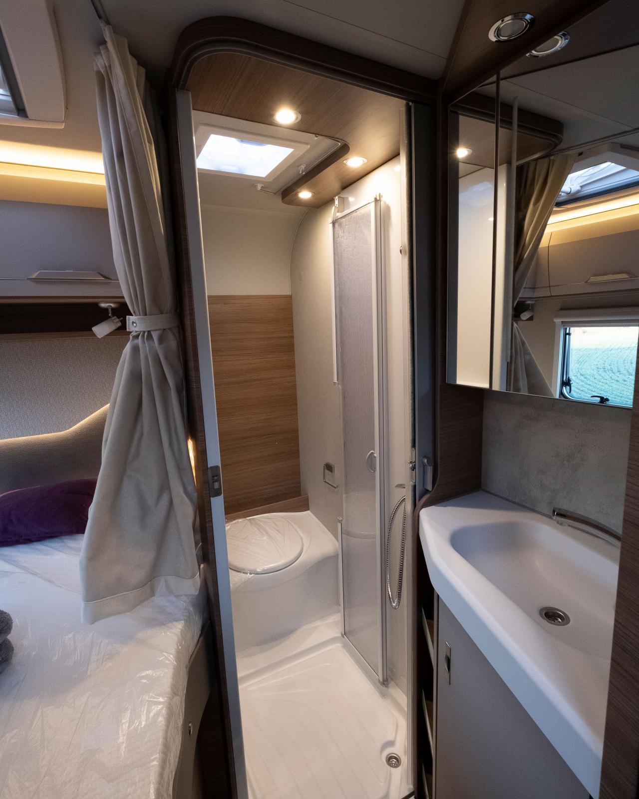 Bänktoa mot bakväggen gör att man får sitta med fötterna i duschkaret. Handfatet placerat utanför ger vissa fördelar.