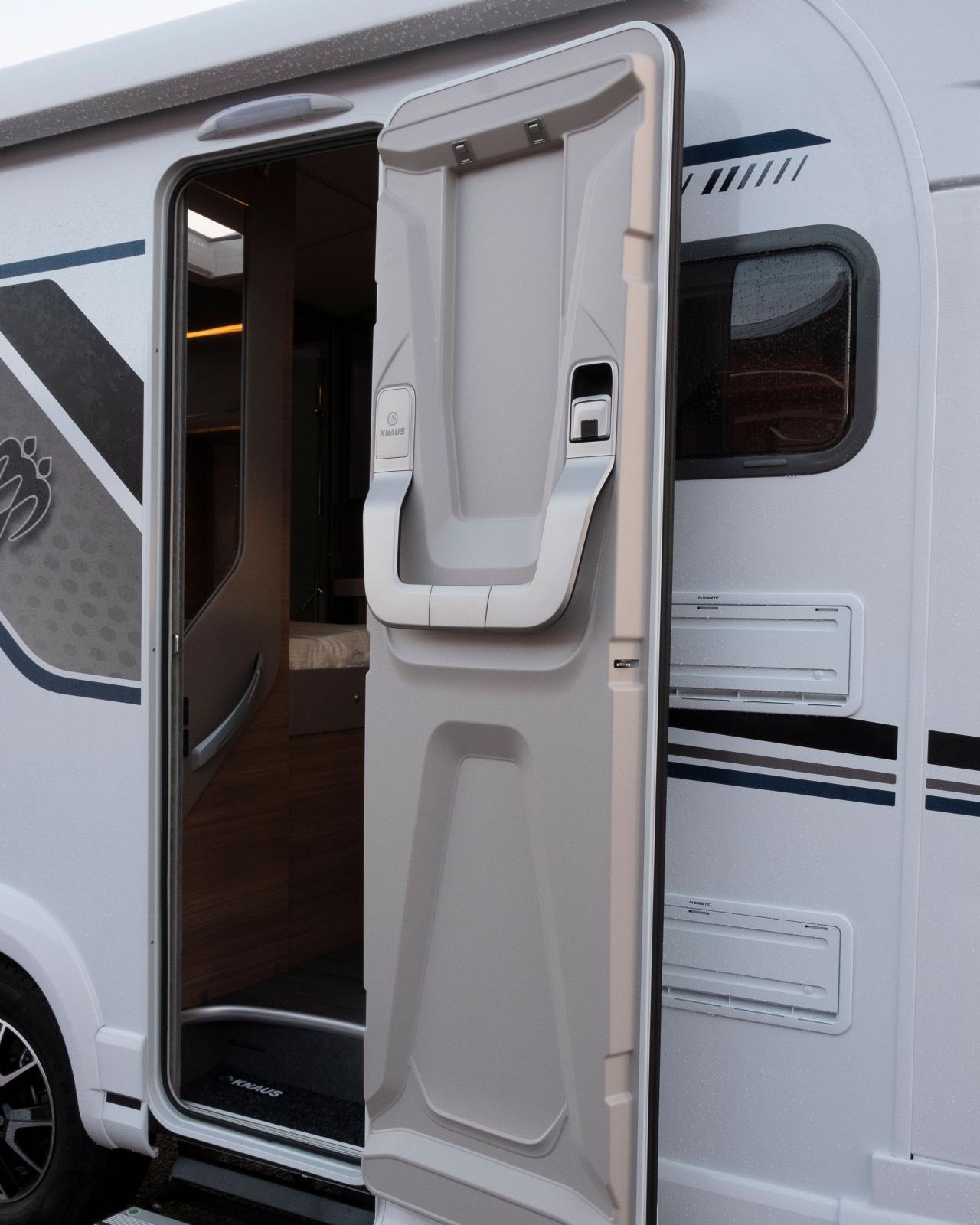 Ett yttre trappsteg och ett inre. Dörren är Knaus enklare modell utan fönster och förvaring men med krokar.