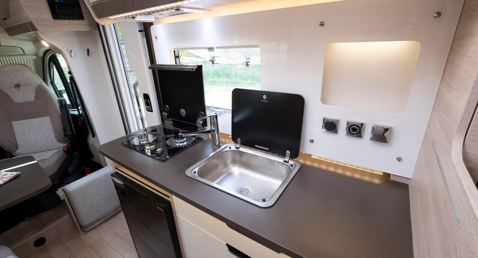 Köket är kompakt utformat men har ändå hyfsad arbetsyta och förvaring. Plastväggen skyddar mot stänk och matos.