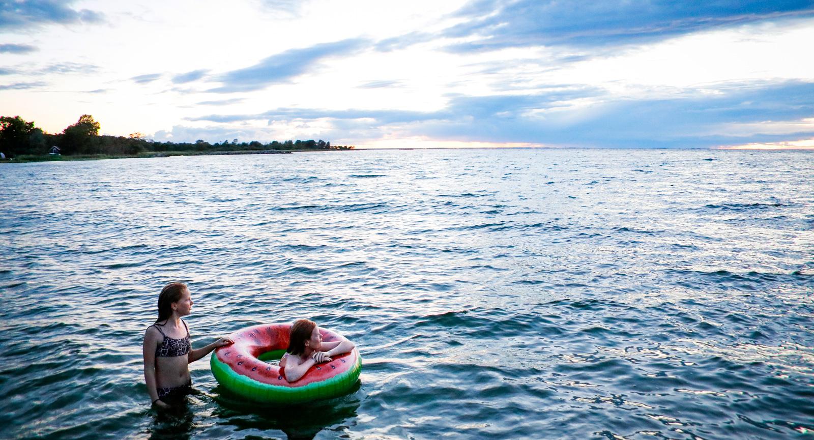 Trots att det är kallt både i luften och i vattnet envisas barnen med att ta ett kvällsdopp efter solnedgången.