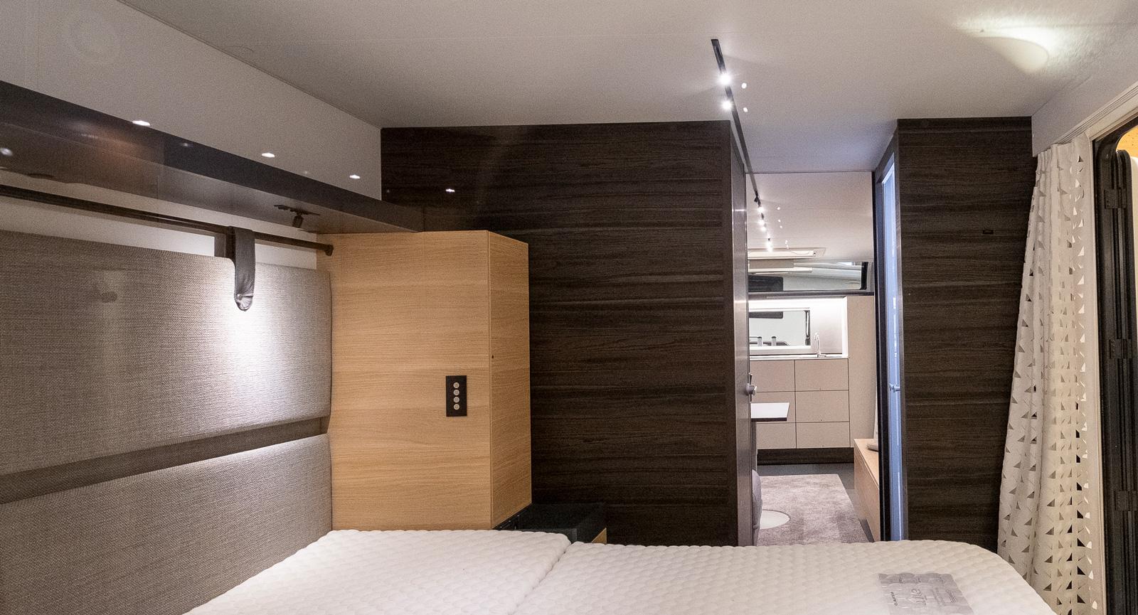 Sovrum med tvärställd queenbed där fotändan är vänd mot den stora öppningen.
