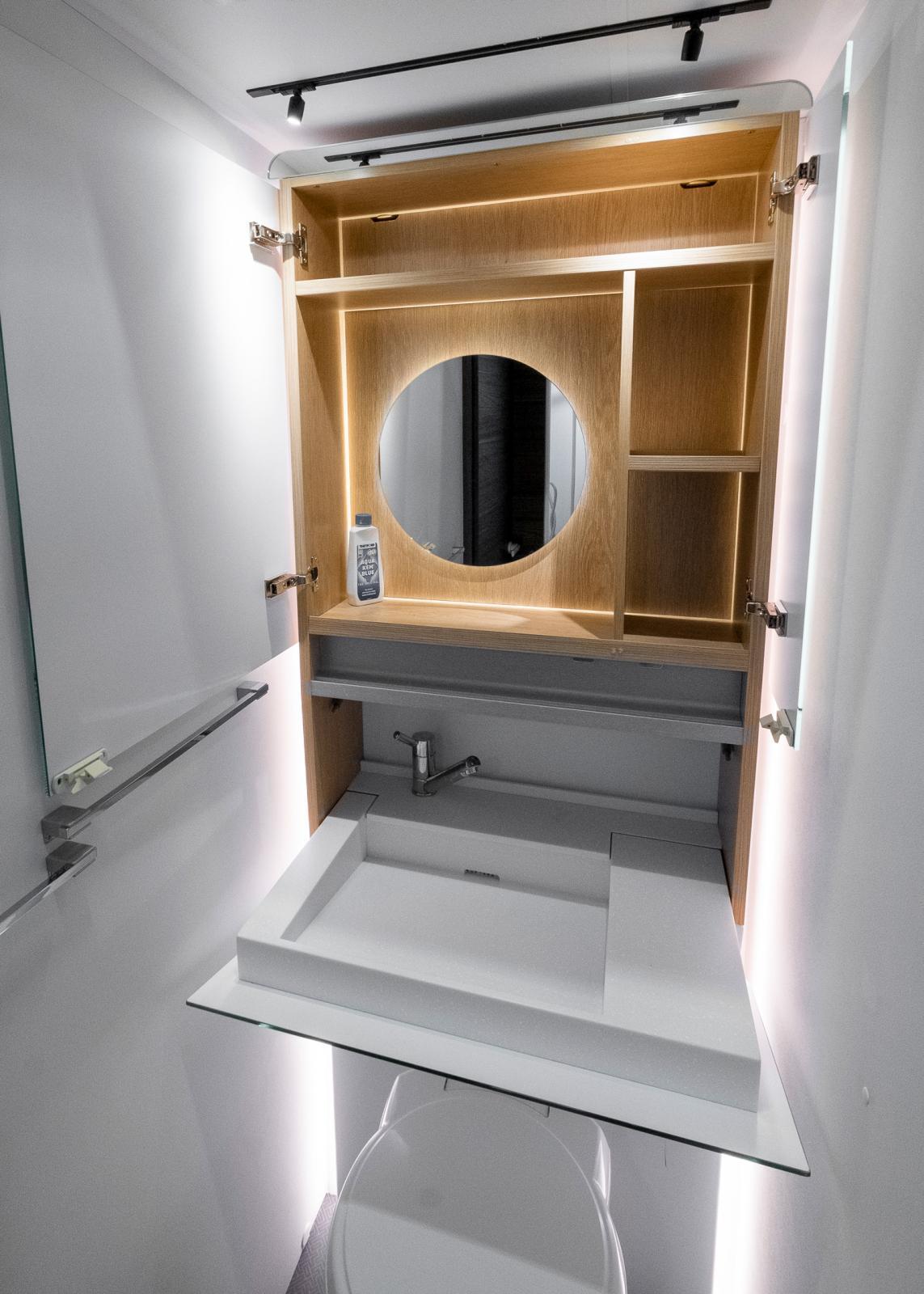 Indirekt belysning, gott om förvaring och nedfällbart handfat gör badrummet både snyggt och praktiskt.