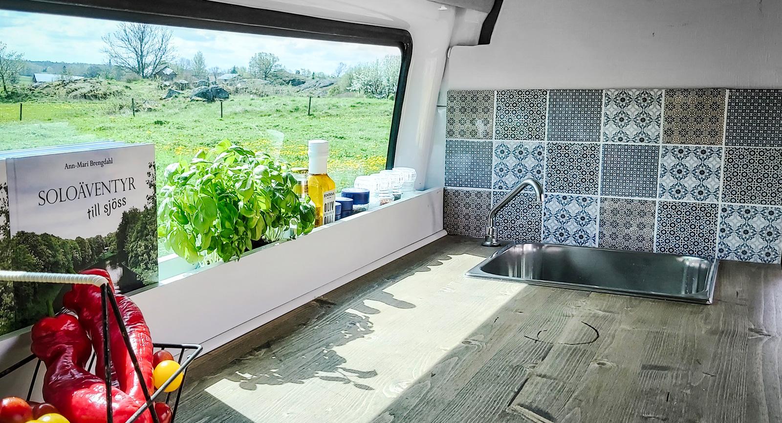Mysigt köksfönster med plats för färska kryddor framför. Kakel som stänkskydd vid diskhon.