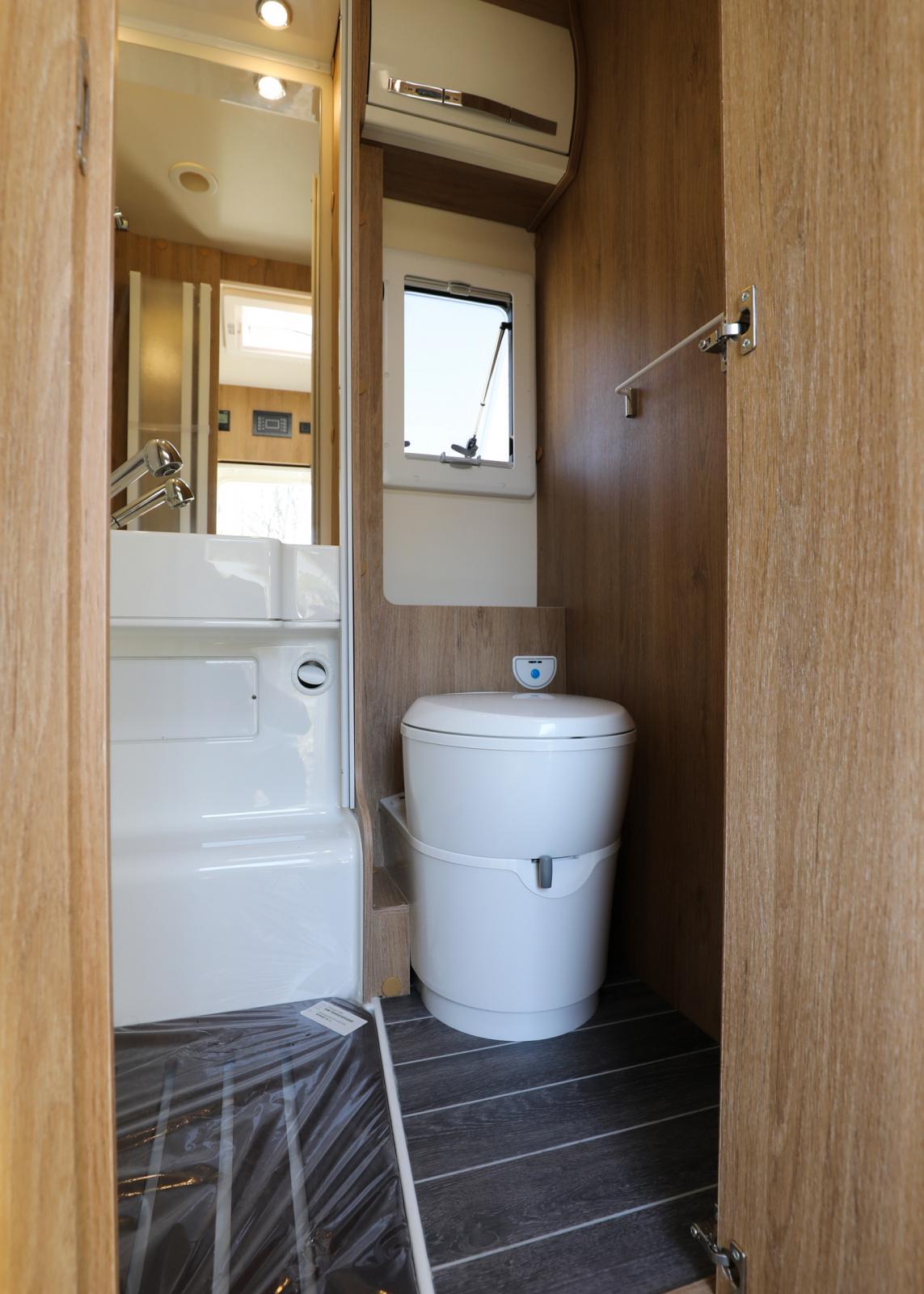 Rymlig toalett och duschkabin med vikbara duschdörrar.