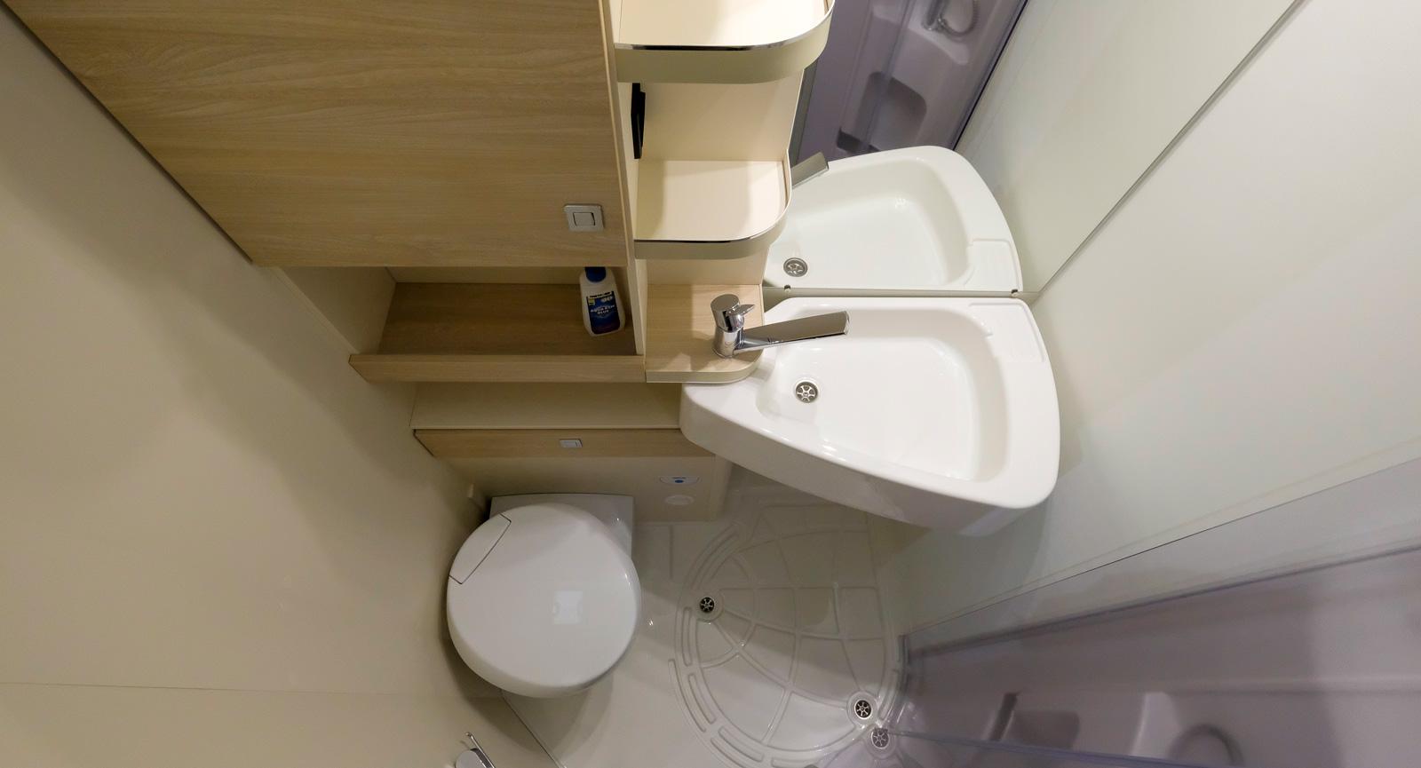 Allt i ett badrum men med smart handfat som kan svängas undan över toaletten innan det ska duschas.