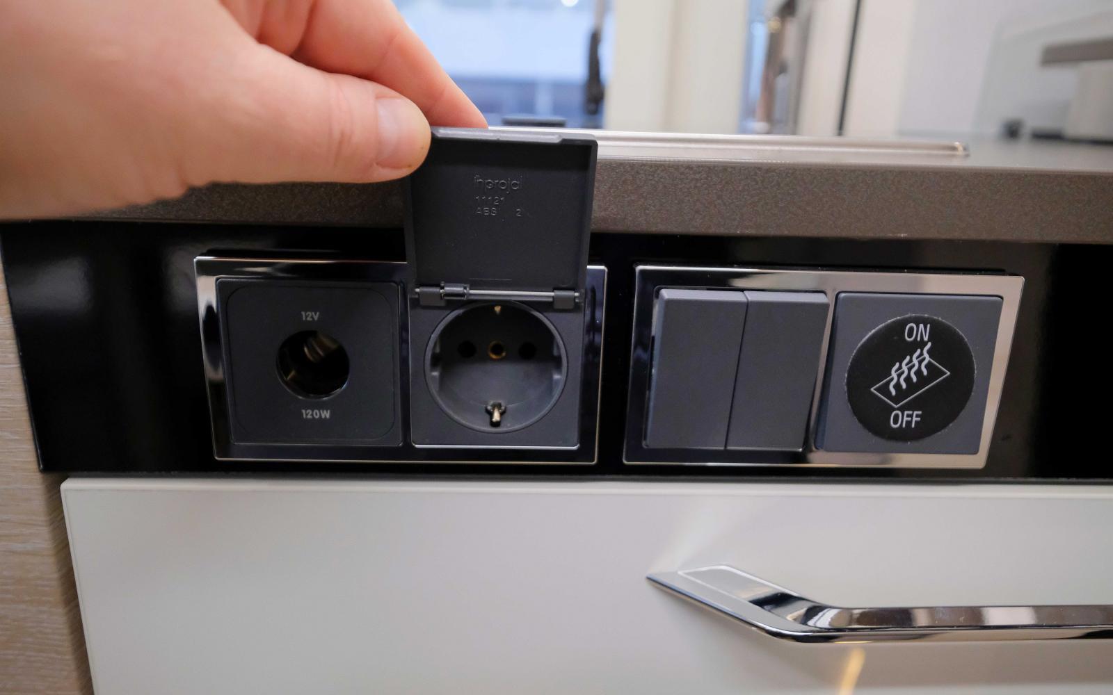 Kontaktuttag, lysknapp och knapp för golvvärme på köksbänkens långsida.