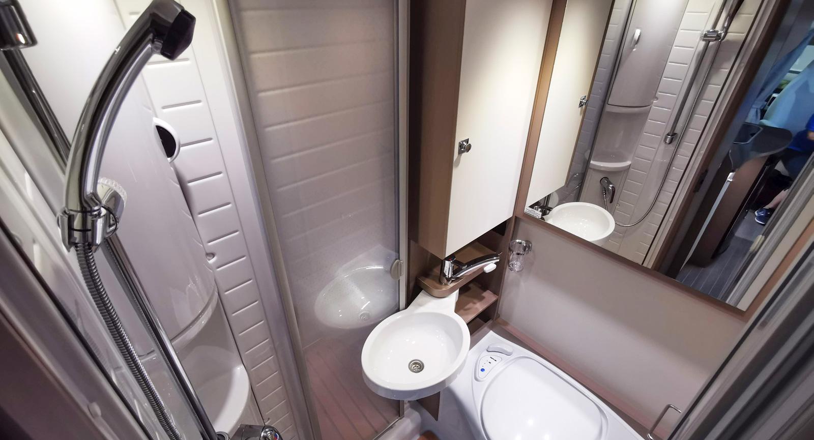 Allt-i-ett badrum med svängbart handfat och duschvägg som stänger av mot toaletten vid duschning.
