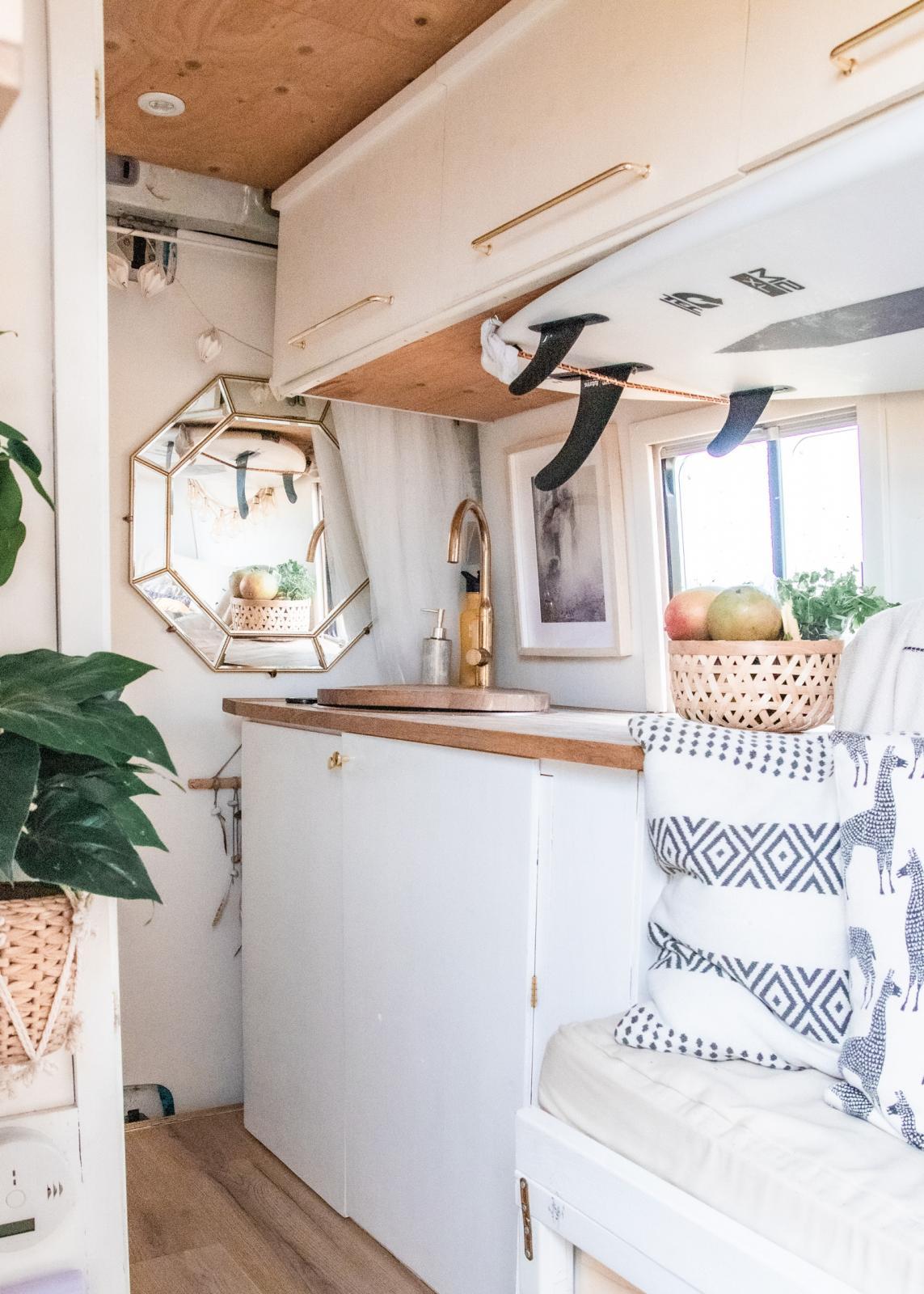 På bakdörren hänger en spegel och ovanför soffan har surfbrädan sin givna plats. Köksbänk och överskåp vid aktern.