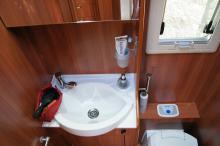 Infälld tvålpump, mandelformat handfat och andra snygga detaljer ger toaletten en trevlig atmosfär.