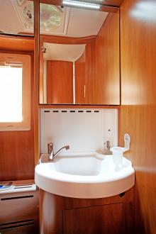 Engreppsblandare och spegelskåp i tvättrummet. Duschen finns i ett avskilt utrymme.