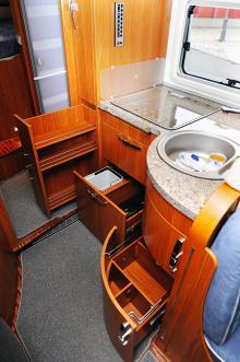 Det vinklade köket är både lättjobbat och välplanerat med välbyggda lådor, bänk i granitimitation och ett fönster över bänken.