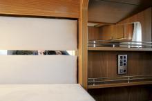 Spegel i sänggaveln, lysknappar och hylla i mitten.