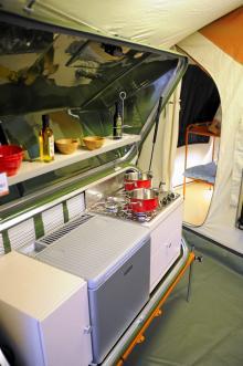 . Köket har kyl, spis och gott om förvaring. Hela köksmodulen placeras på släpets dragstång under transport. I bakgrunden syns ett extra sovrum med våningssäng.