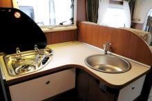 Köket är trevligt utformat med bra avställningsyta. Dock i enklaste laget utan vare sig avrinningsyta vid diskhon eller besticklåda i utdragslådorna. Köksfläkt saknas men inte köksfönster.