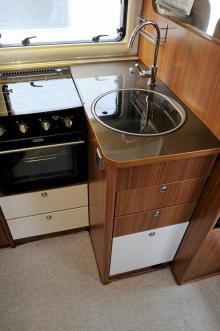 Köket i vinkel är snyggt utformat. Längst bort på köksbänken syns en liten lucka som döljer en avfallshink. Avrinningsyta saknas men glasluckor över spis och diskho ger mer utrymme.