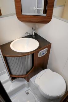Vattenklosett med elektrisk spolning. Gott om speglar och förvaring. Duschkabinen är placerad till vänster utanför bild.