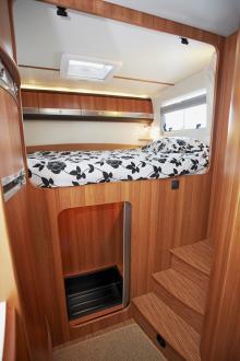 Sängen är tvärställd och ganska högt belägen. Till hjälp finns en trappa upp. Under sängen finns en garderob.