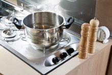 Köket är i minsta laget men här finns ändå möjligheten att laga enklare rätter. En glasskiva täcker spis och diskho.