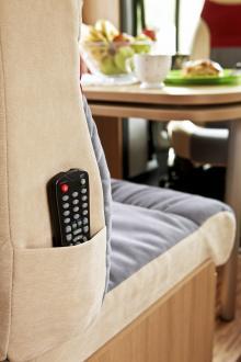 Matbordet har en extra skiva som kan svängas ut närmare passagerarstolen. Bakom fotografen finns ett tv-stativ som också går att svänga runt om man vill se på tv från den bakre dubbelsängen.