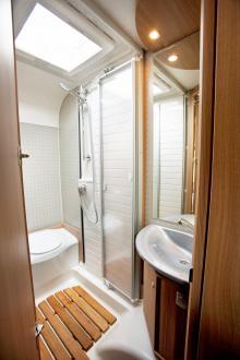 Toaletten är rymlig med dusch i mitten som avgränsas med dubbla plastdörrar.