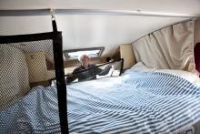 Näten skyddar sovande från att ramla ner. Sängen går att bädda åt båda hållen, men sänglampor finns bara infällda i taket till vänster på bilden. Takfönster och hyllor finns inom räckhåll.